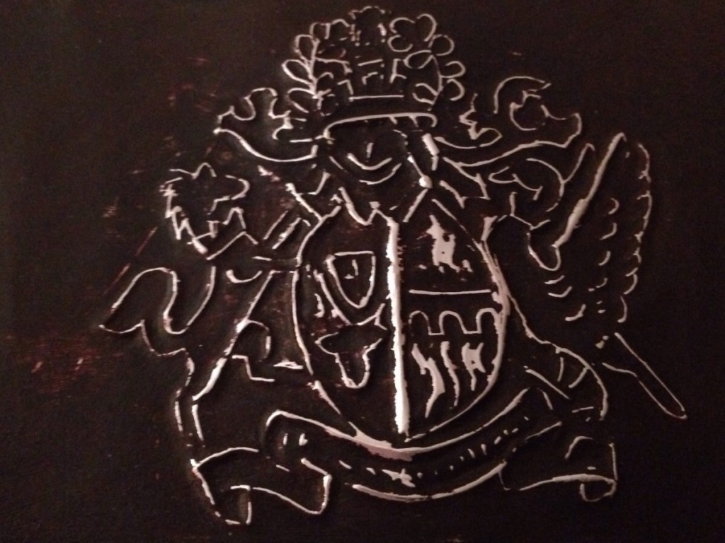 A finished embossed metal coat of arms